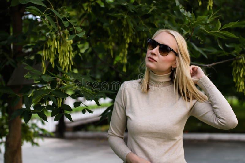 Mujer rubia joven en las gafas de sol que presentan en la calle imagen de archivo