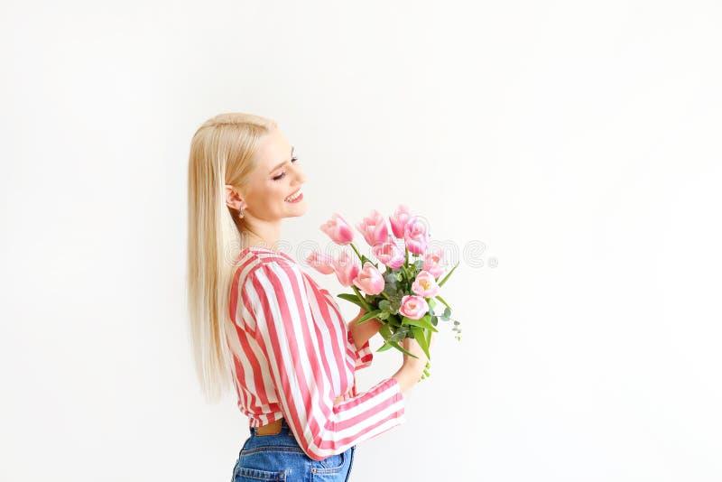 Mujer rubia joven en vaqueros de la mam? y el ramo de la tenencia del camiseta top de la cosecha de tulipanes fotos de archivo libres de regalías