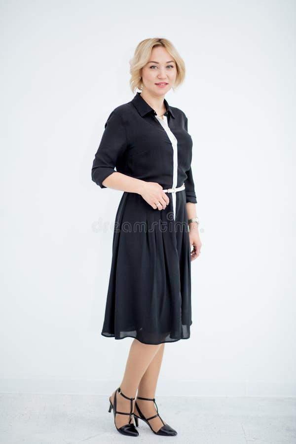 Mujer rubia joven en vestido negro formal en el fondo blanco fotos de archivo
