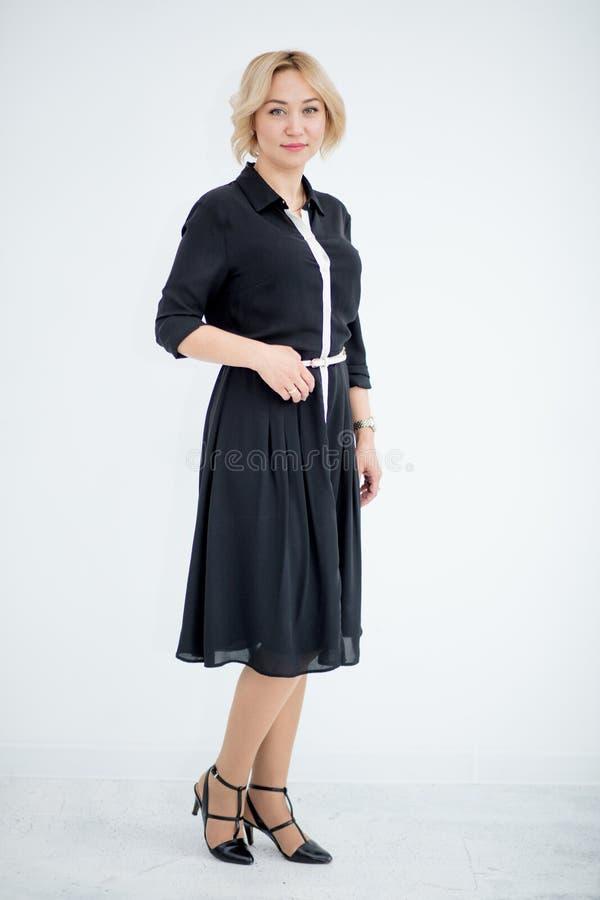 Mujer rubia joven en vestido negro formal en el fondo blanco imagen de archivo
