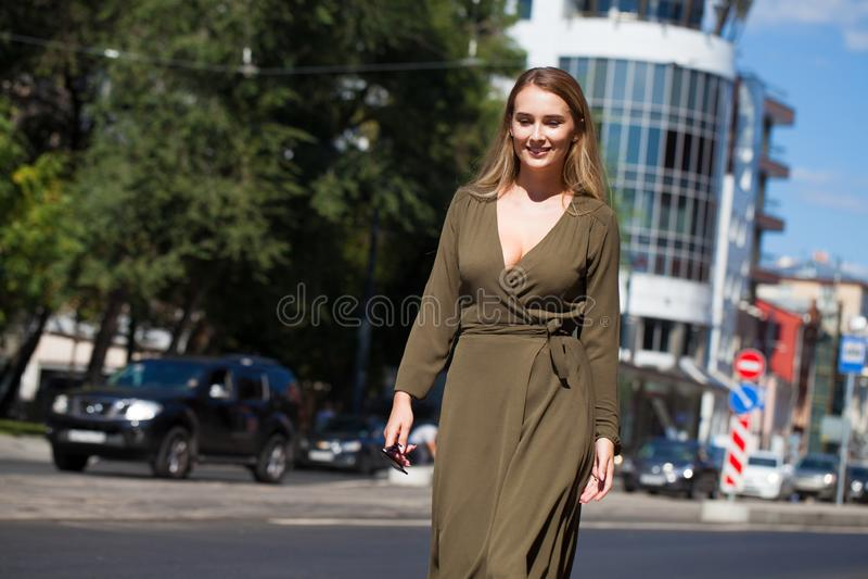 Mujer rubia joven en vestido que camina en calle del verano imagen de archivo