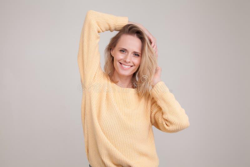 Mujer rubia joven encantadora bonita hermosa en suéter amarillo que sonríe feliz, divirtiéndose dentro, jugando con su pelo recto imagen de archivo