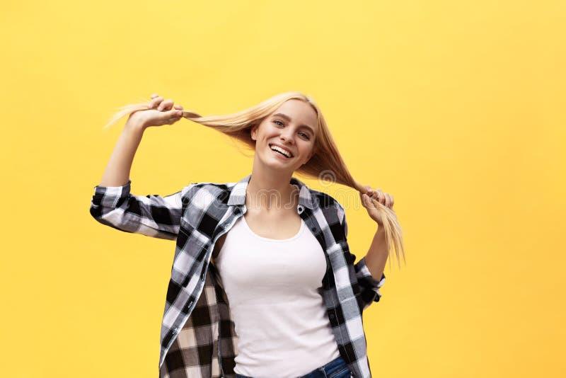 Mujer rubia joven encantadora bonita hermosa que sonríe feliz, divirtiéndose dentro, jugando con el pelo recto largo fotografía de archivo