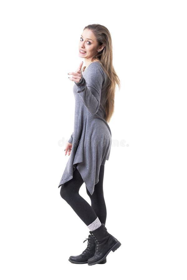 Mujer rubia joven expresiva divertida linda que camina y que señala en la cámara Vista lateral imágenes de archivo libres de regalías