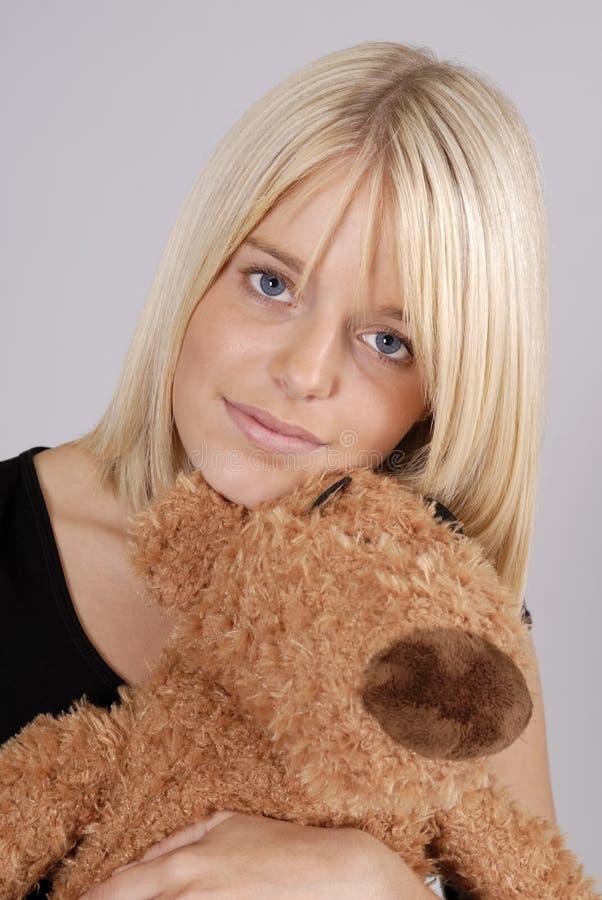 Mujer rubia joven hermosa con el oso de peluche imagen de archivo