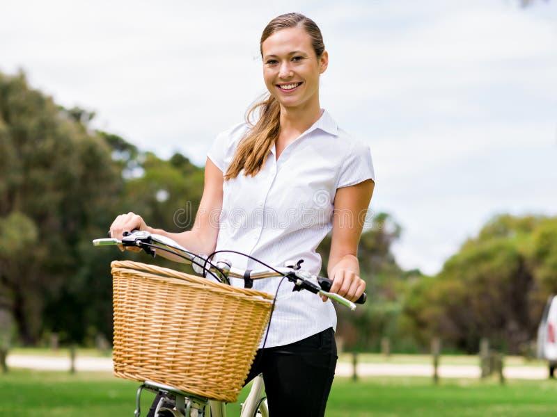 Mujer rubia joven hermosa con la bici en parque fotos de archivo libres de regalías