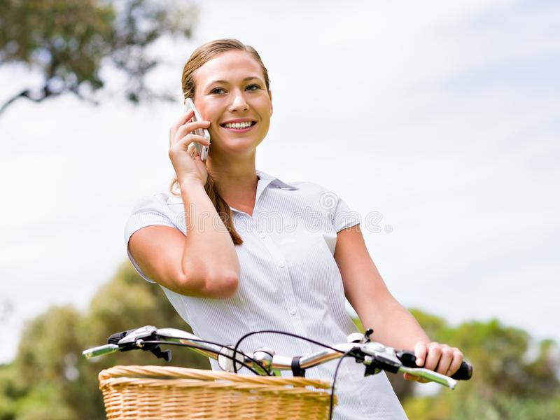 Mujer rubia joven hermosa con la bici en parque que habla sobre el teléfono fotografía de archivo libre de regalías