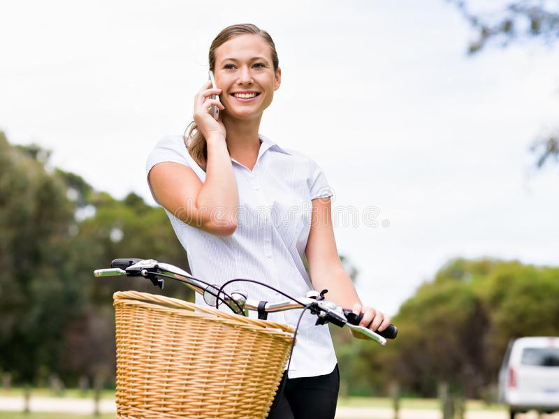 Mujer rubia joven hermosa con la bici en parque que habla sobre el teléfono fotos de archivo
