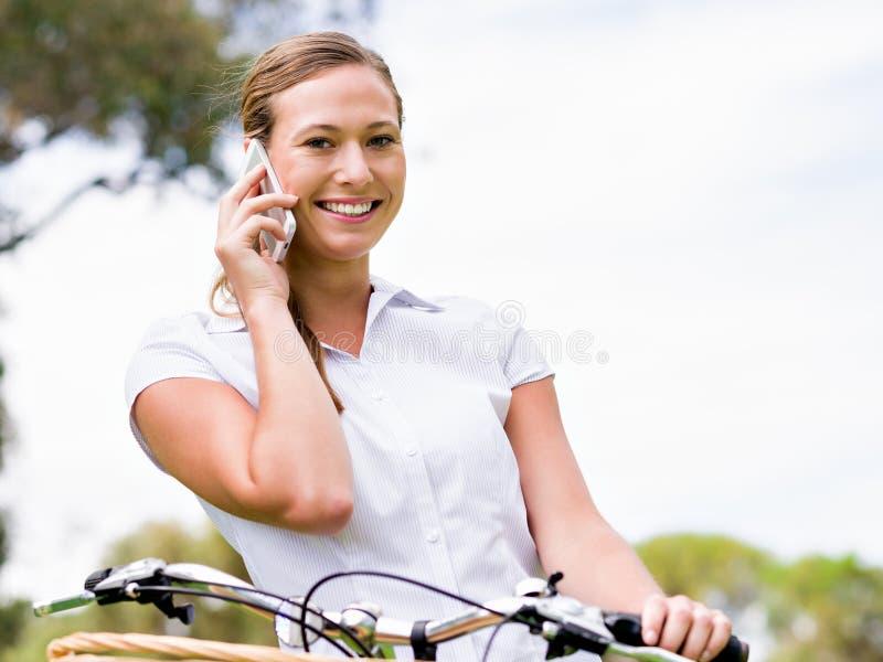 Mujer rubia joven hermosa con la bici en parque que habla sobre el teléfono foto de archivo libre de regalías