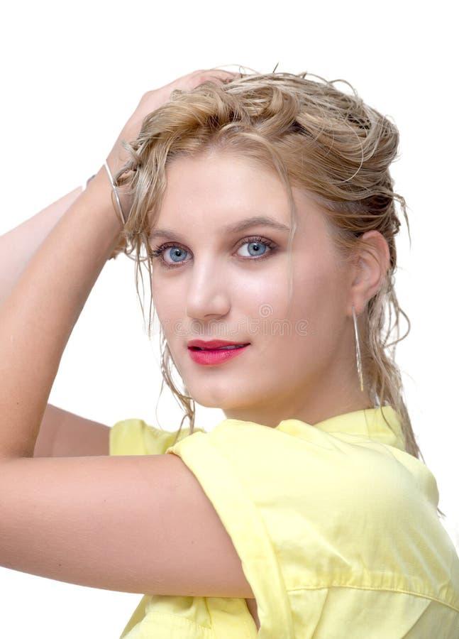 Mujer rubia joven hermosa con la camisa amarilla en el backgro blanco imagen de archivo