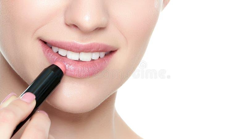 Mujer rubia joven hermosa con los labios llenos atractivos que aplican el lápiz labial coralino del color Retrato de la belleza a fotos de archivo libres de regalías