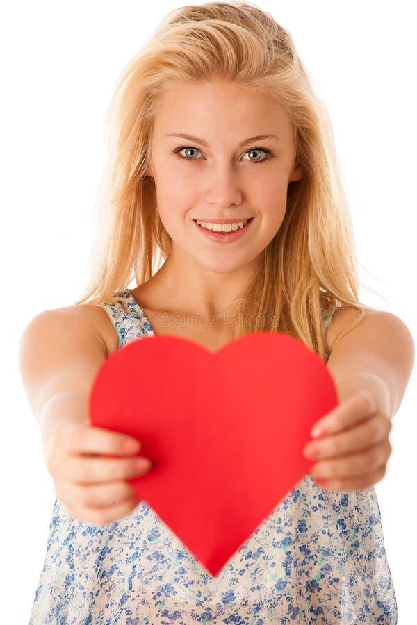 Mujer rubia joven hermosa con los ojos azules que llevan a cabo la prohibición roja del ciervo foto de archivo libre de regalías