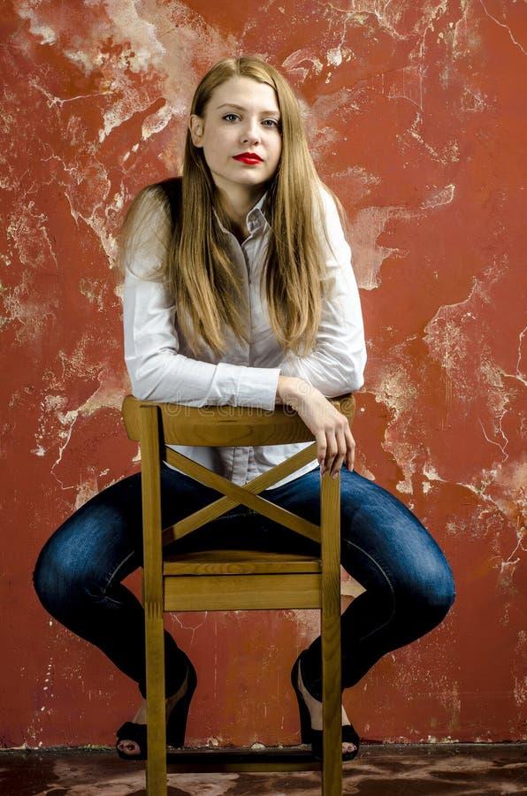 Mujer rubia joven hermosa delgada joven con las piernas y el pelo largos en camisa y vaqueros del alboroto imagenes de archivo