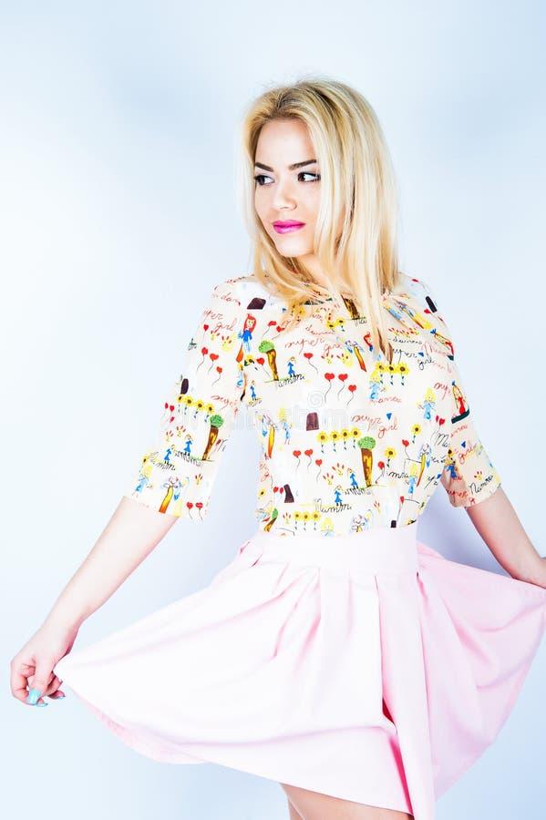 Mujer rubia joven hermosa en el vestido agradable de la primavera, presentando en el fondo blanco, estudio fotografía de archivo