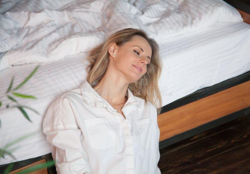 Mujer rubia joven hermosa en la cama en casa fotografía de archivo
