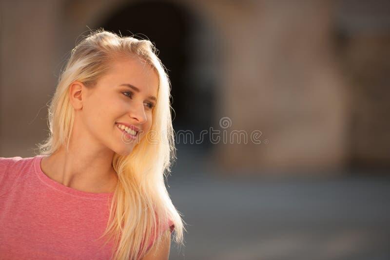 Mujer rubia joven hermosa en un arownd del paseo la ciudad cerca al castillo en día soleado del verano imagen de archivo