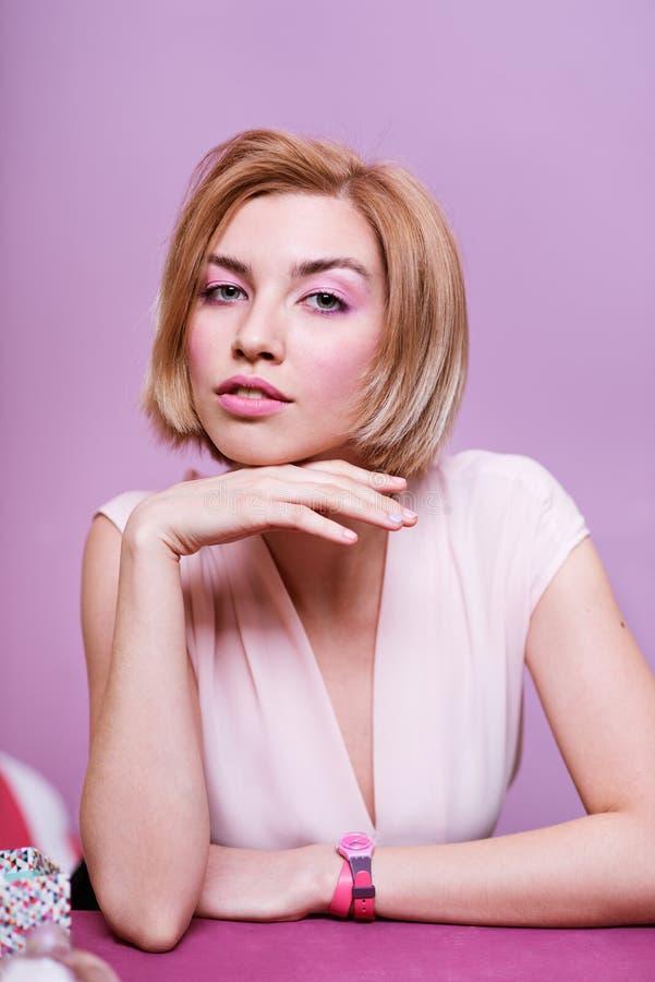 Mujer rubia joven hermosa en una tabla con los postres fotografía de archivo libre de regalías