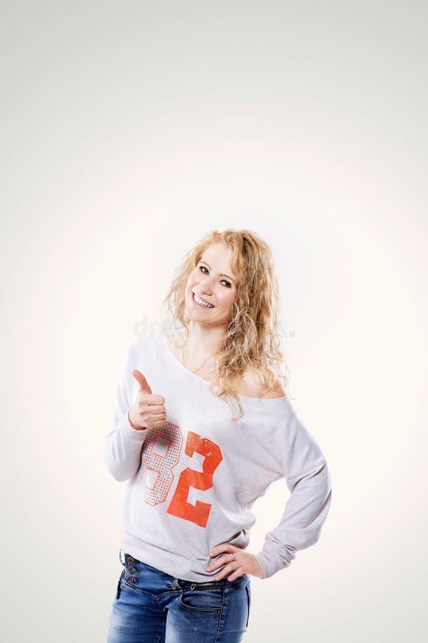 Mujer rubia joven hermosa en vaqueros y mostrar de la camiseta pulgares para arriba encendido imagen de archivo libre de regalías