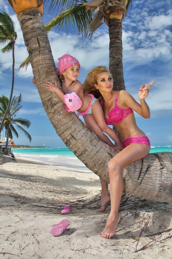 Mujer rubia joven hermosa lunes que se sienta en el tronco de una palmera con la hija, princesa de la niña fotografía de archivo libre de regalías