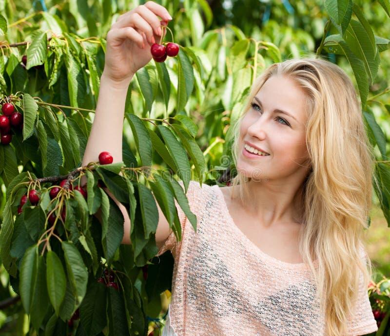 Mujer rubia joven hermosa que cosecha cerezas en aguas termales fotos de archivo libres de regalías