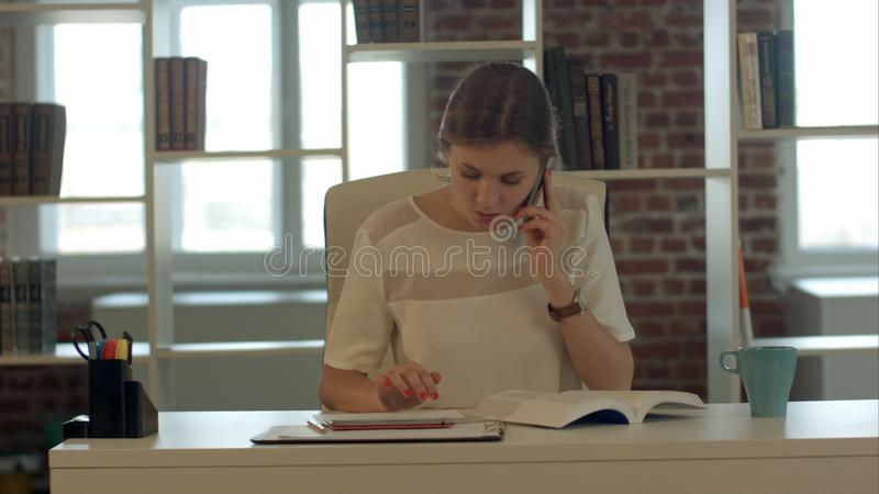 Mujer rubia joven hermosa que habla en el teléfono móvil y el libro de lectura fotos de archivo libres de regalías