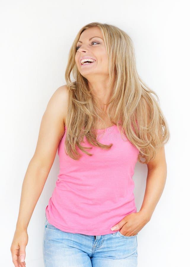 Mujer rubia joven hermosa que ríe y que mira para arriba imagen de archivo