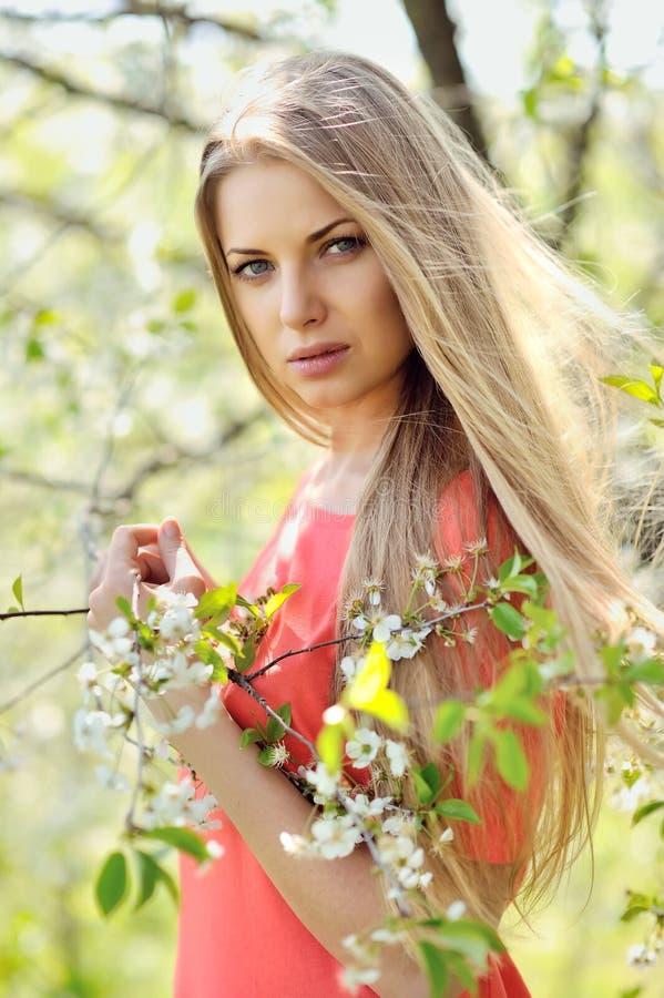 Mujer rubia joven hermosa que se coloca cerca de árbol floreciente fotos de archivo libres de regalías
