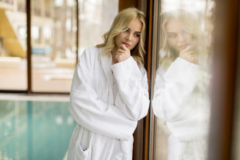 Mujer rubia joven hermosa que se relaja en la piscina interior imagenes de archivo