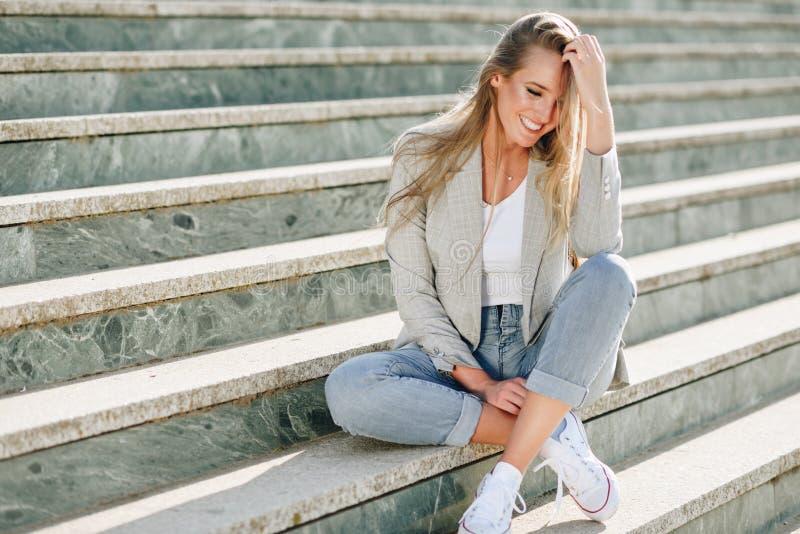 Mujer rubia joven hermosa que sonríe en pasos urbanos fotos de archivo
