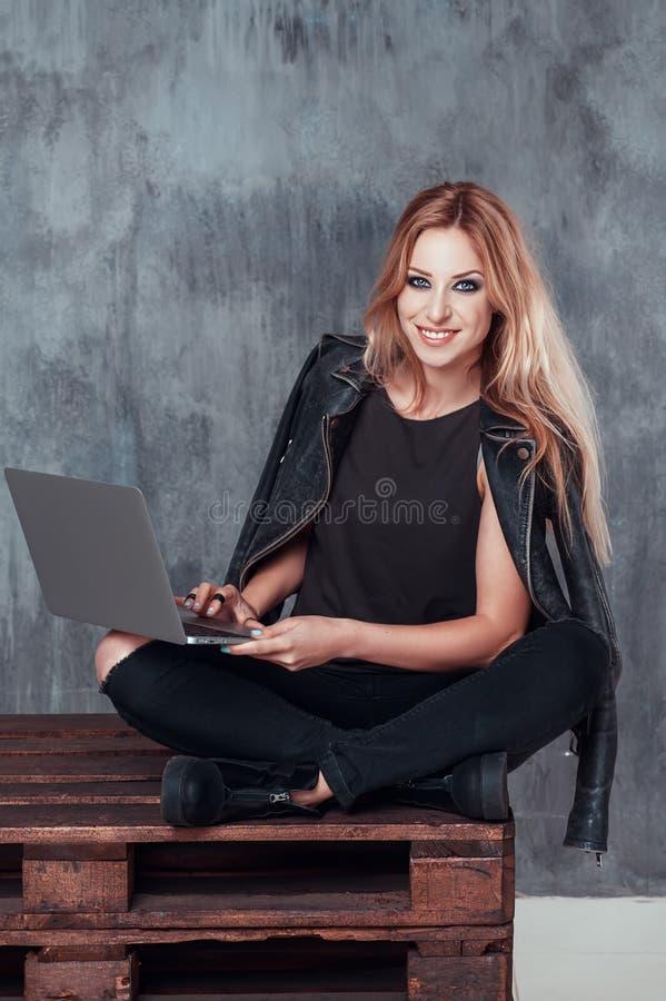 Mujer rubia joven hermosa que usa el ordenador portátil portátil mientras que se sienta en un lugar del vintage Sonrisa del estud imagenes de archivo