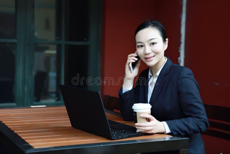Mujer rubia joven hermosa seria de la mujer de negocios que habla en el teléfono celular móvil que trabaja en un ordenador de la  foto de archivo libre de regalías