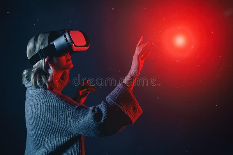 Mujer rubia joven hermosa vidrios de un VR que llevan que tocan el objeto imaginario en aire durante la experiencia de la realida foto de archivo libre de regalías