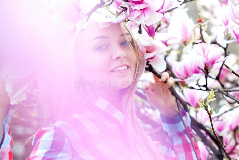 Mujer rubia joven maravillosa que sonríe en flores florecientes del rosa fotografía de archivo