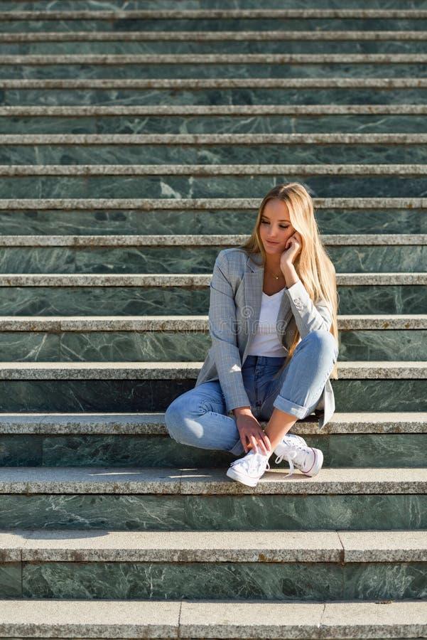 Mujer rubia joven pensativa que se sienta en pasos urbanos imágenes de archivo libres de regalías