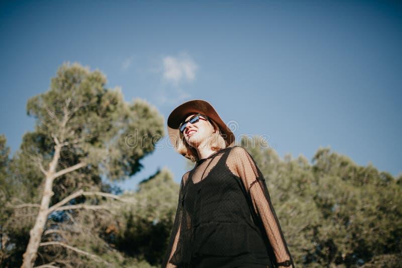 Mujer rubia joven que camina en naturaleza con las lentes de sol negros y ropa y un sombrero fotos de archivo libres de regalías
