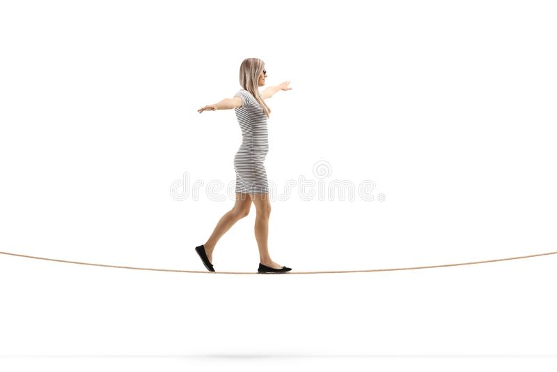 Mujer rubia joven que camina en una cuerda con la extensión de los brazos fotografía de archivo