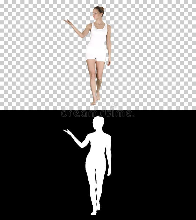 Mujer rubia joven que camina y que señala para echar a un lado mostrando en algo, Alpha Channel imagenes de archivo