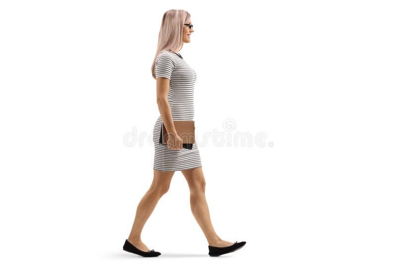 Mujer rubia joven que camina y que sostiene los libros fotos de archivo