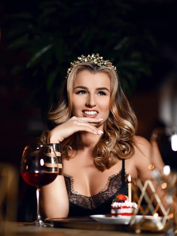 Mujer rubia joven que come el desierto de la torta de la fresa en un restaurante del café en el tiempo de igualación que celebra  foto de archivo libre de regalías