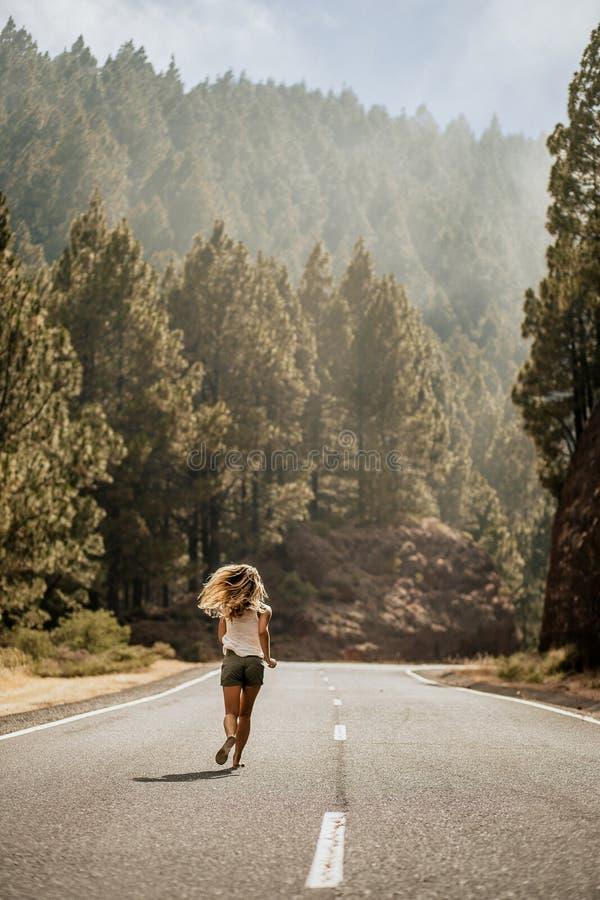 Mujer rubia joven que corre en chancletas en el camino vacío a lo largo del tiempo de verano más forrest lifestyle Sígame Visión  fotografía de archivo libre de regalías