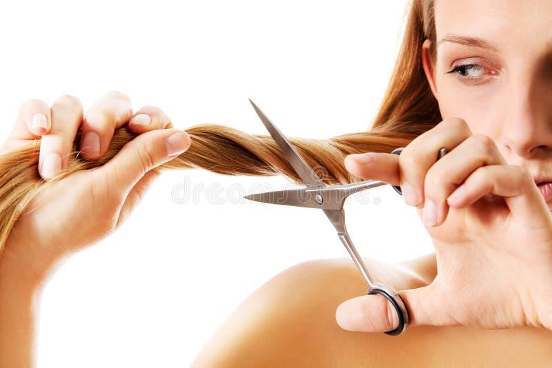 Mujer rubia joven que corta su pelo con las tijeras imágenes de archivo libres de regalías