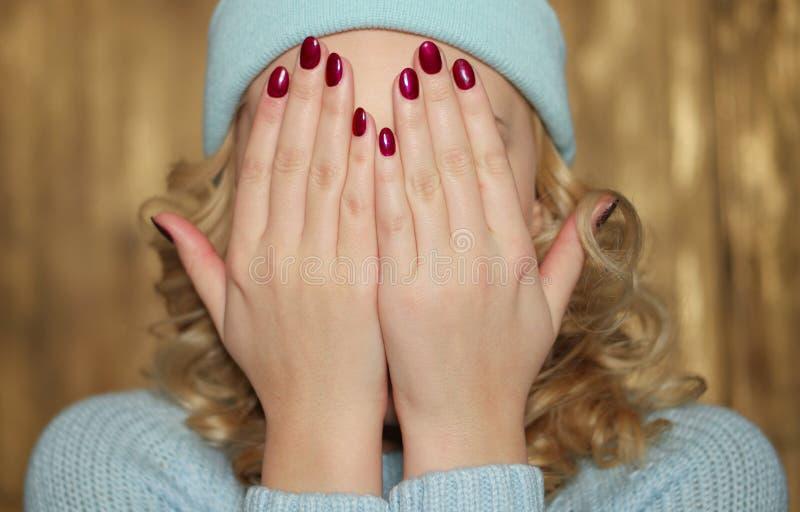 Mujer rubia joven que cubre su cara foto de archivo libre de regalías
