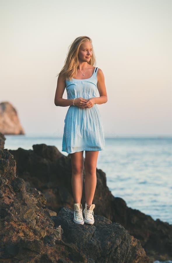 Mujer rubia joven que defiende en rocas el mar imagenes de archivo
