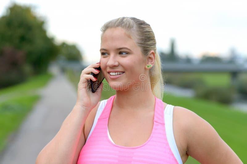 Mujer rubia joven que habla en el teléfono al aire libre fotos de archivo