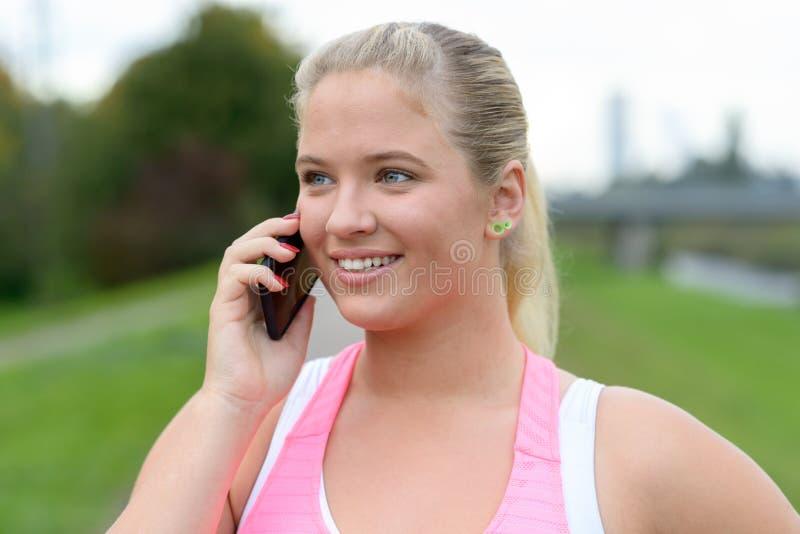 Mujer rubia joven que habla en el teléfono al aire libre imagenes de archivo