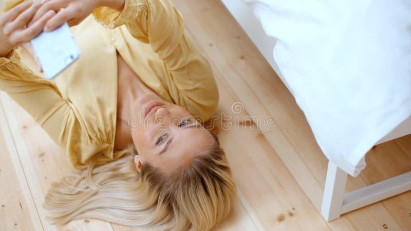 Mujer rubia joven que hace el selfie mientras que miente en un piso imagen de archivo libre de regalías