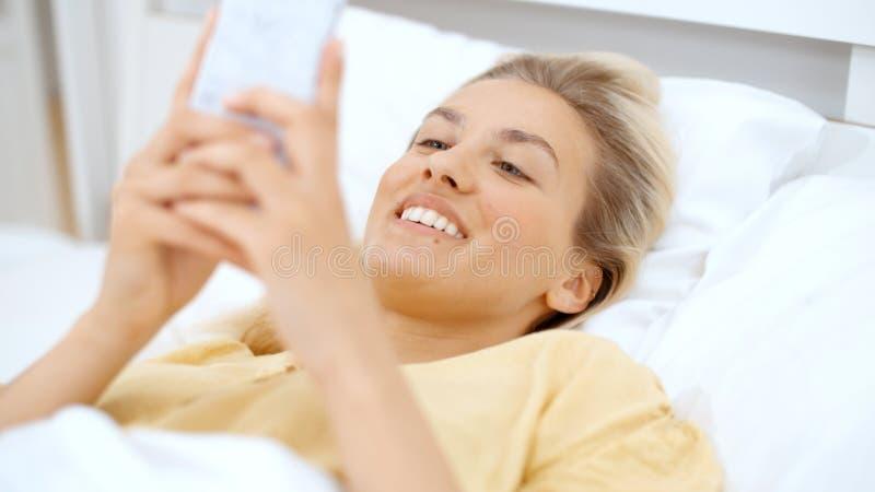 Mujer rubia joven que mecanografía en el teléfono mientras que miente en una cama imagen de archivo