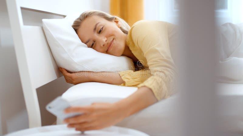 Mujer rubia joven que mecanografía en el teléfono mientras que miente en una cama fotos de archivo