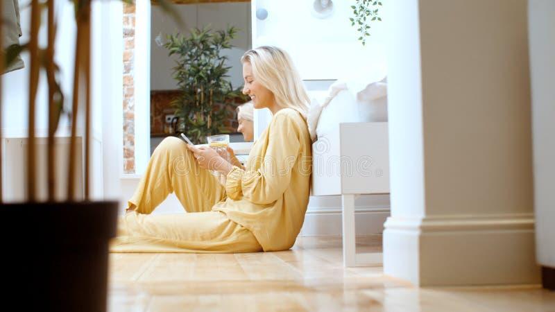 Mujer rubia joven que mecanografía en el teléfono mientras que se sienta en un piso foto de archivo