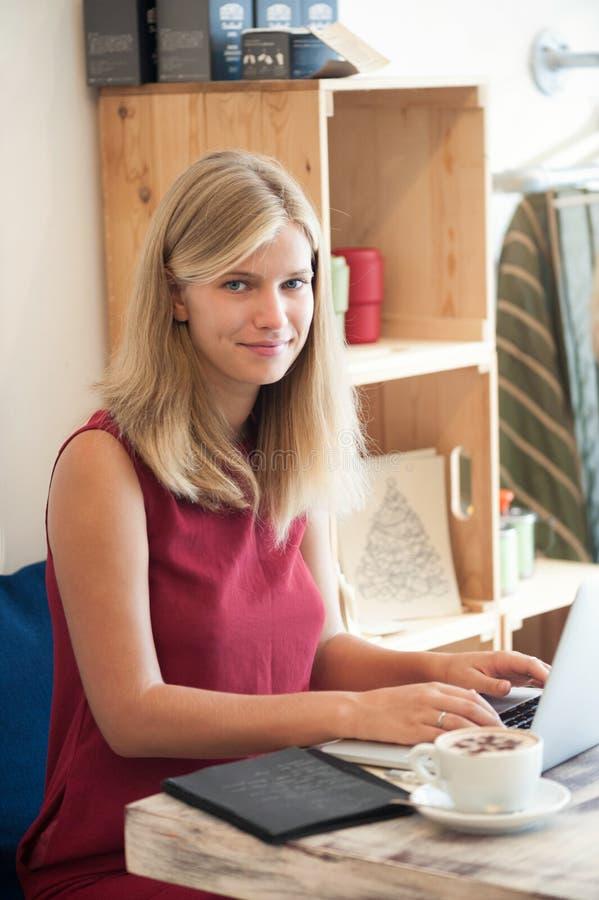 Mujer rubia joven que mecanografía en ordenador portátil en café foto de archivo